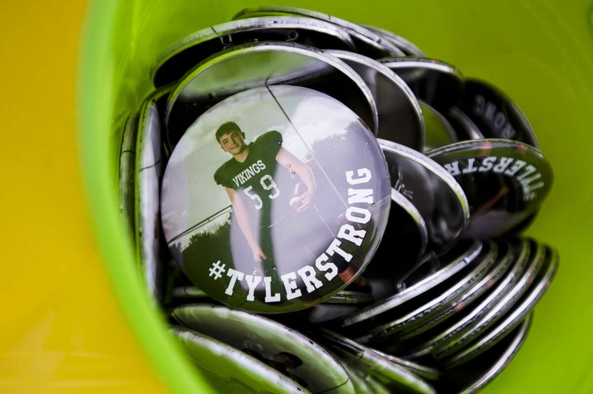 Buttons supporting Tyler Wirth, an eighth-grader at Northeast Middle School who was recently diagnosed with stage 4 cancer, are sold during a fundraiser for the Wirth family organized by Amanda Page before a football game between Northeast and Jefferson middle schools on Wednesday, Oct. 17, 2018. (Katy Kildee/kkildee@mdn.net)