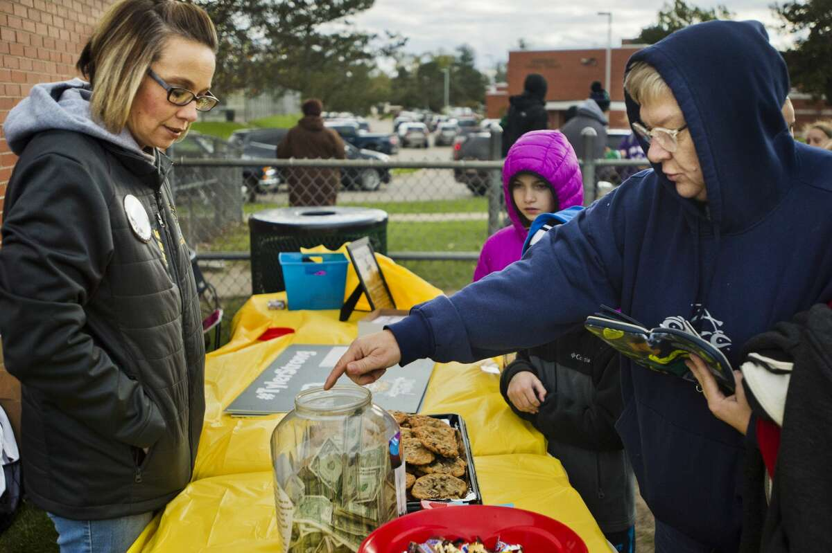 Sally Bukoski, right, places a donation into a container during a fundraiser organized by Amanda Page, left, for Tyler Wirth, an eighth-grader at Northeast Middle School who was recently diagnosed with stage 4 cancer, before a football game between Northeast and Jefferson middle schools on Wednesday, Oct. 17, 2018. (Katy Kildee/kkildee@mdn.net)