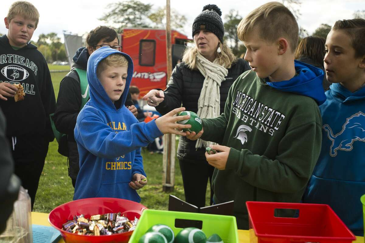 Children choose items to buy during a fundraiser for Tyler Wirth, an eighth-grader at Northeast Middle School who was recently diagnosed with stage 4 cancer, before a football game between Northeast and Jefferson middle schools on Wednesday, Oct. 17, 2018. (Katy Kildee/kkildee@mdn.net)