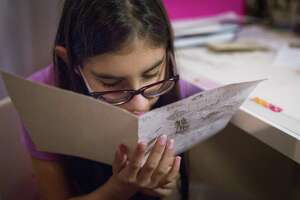 Sophia Salehi, 9, gets close to read an illustrated story she wrote and illustrated, Saturday, Dec. 17, 2016, in her home in Pearland. Salehi was born prematurely and is a surviving twin. She is also legally blind but she was denied special education services by Houston Independent School District. ( Marie D. De Jesus / Houston Chronicle )