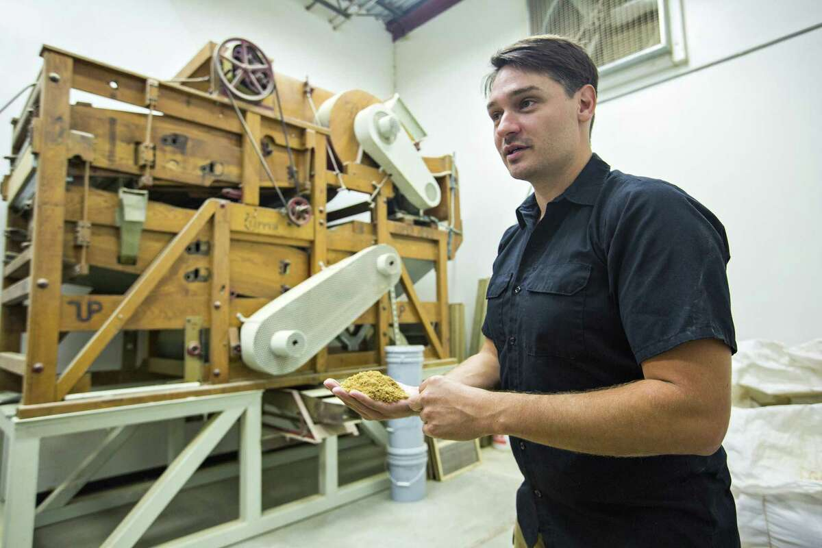 Brandon Ade, founder of Blacklands Malt, holds some byproducts of the grains in the sorting room at Blacklands Malt in Leander.