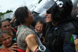 Honduran migrants heading in a caravan to the US, hold up a crying baby while they struggle to cross one of the gates of the Guatemala-Mexico international border bridge in Ciudad Hidalgo, Chiapas state, Mexico, on October 19, 2018. - Honduran migrants who have made their way through Central America were gathering at Guatemala's northern border with Mexico on Friday, despite President Donald Trump's threat to deploy the military to stop them entering the United States.