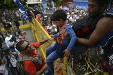 A child is carried over the border fence as thousands of Honduran migrants rush across the border towards Mexico, in Tecun Uman, Guatemala, Friday, Oct. 19, 2018. Migrants broke down the gates at the border crossing and began streaming toward a bridge into Mexico. After arriving at the tall, yellow metal fence some clambered atop it and on U.S.-donated military jeeps. Young men began violently tugging on the barrier and finally succeeded in tearing it down.