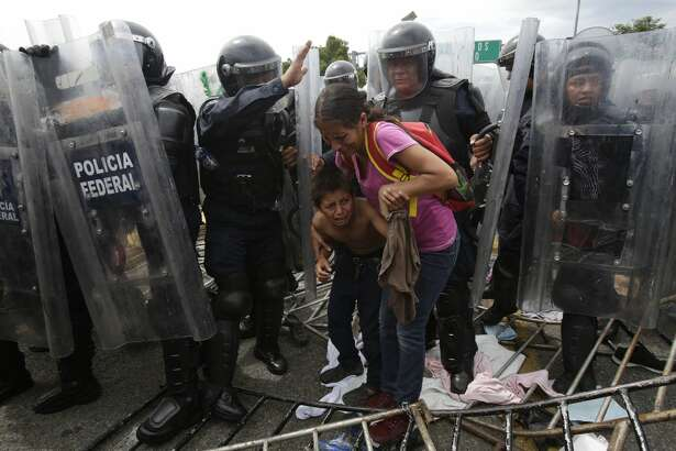 A Honduran migrant mother and child cower in fear as they are surrounded by Mexican Federal Police in riot gear, at the border crossing in Ciudad Hidalgo, Mexico, Friday, Oct. 19, 2018. Central Americans traveling in a mass caravan broke through a Guatemalan border fence and streamed by the thousands toward Mexican territory, defying Mexican authorities' entreaties for an orderly migration and U.S. President Donald Trump's threats of retaliation.