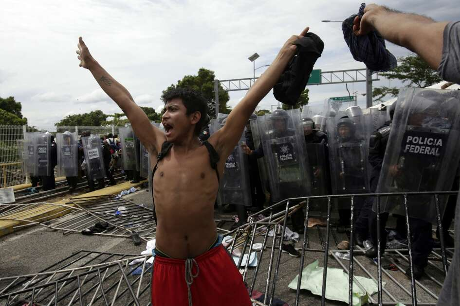 A youth calls for calm as he stands in from of a phalanx of Mexican Federal Police in riot gear, after Central American migrants rushed the gate at the border crossing in Ciudad Hidalgo, Mexico, Friday, Oct. 19, 2018. Central Americans traveling in a mass caravan broke through a Guatemalan border fence and streamed by the thousands toward Mexican territory, defying Mexican authorities' entreaties for an orderly migration and U.S. President Donald Trump's threats of retaliation.