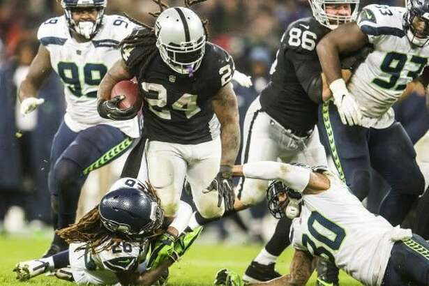 Oakland Raiders running back Marshawn Lynch is stopped by Seattle Seahawks cornerback Shaquill Griffin and strong safety Bradley McDougald in the second half on Sunday, Oct. 14, 2018 at Wembley Stadium in London, England. (Bettina Hansen/Seattle Times/TNS)
