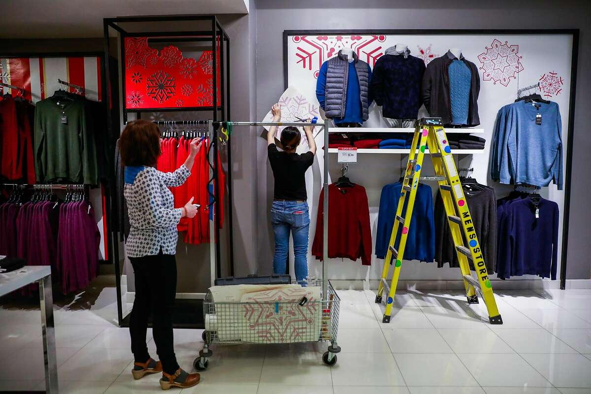 Sales colleagues put the finishing touches on a display in the men's department at Macy's in San Francisco, California, on Tuesday, Oct. 16, 2018.
