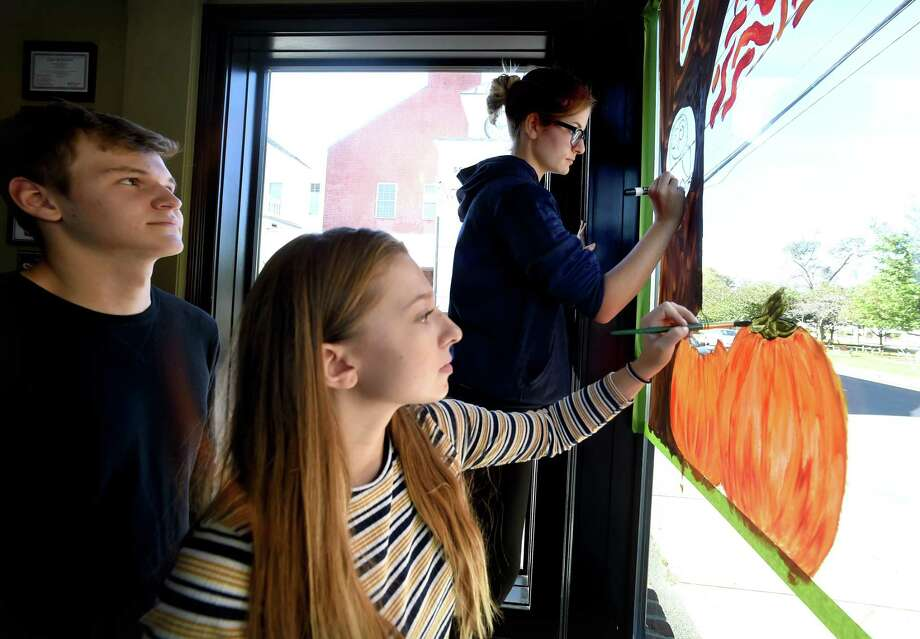 From left, Platt Technical High School seniors Evan Mazako watches Taylor Krieder and Zoe Paskiewicz paint a Halloween theme in the front window of the Colony Grill on Broad Street in Milford on October 19, 2018. Photo: Arnold Gold / Hearst Connecticut Media / New Haven Register