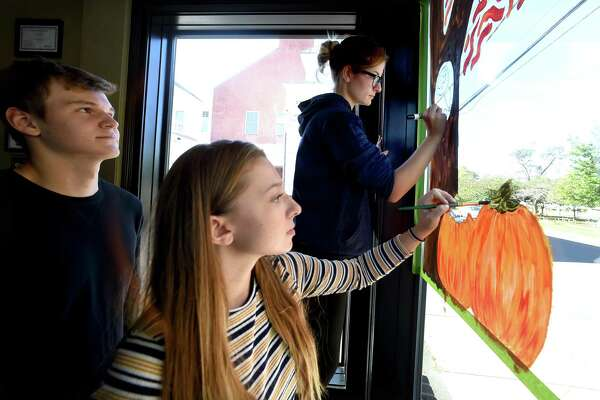 From left, Platt Technical High School seniors Evan Mazako watches Taylor Krieder and Zoe Paskiewicz paint a Halloween theme in the front window of the Colony Grill on Broad Street in Milford on October 19, 2018.