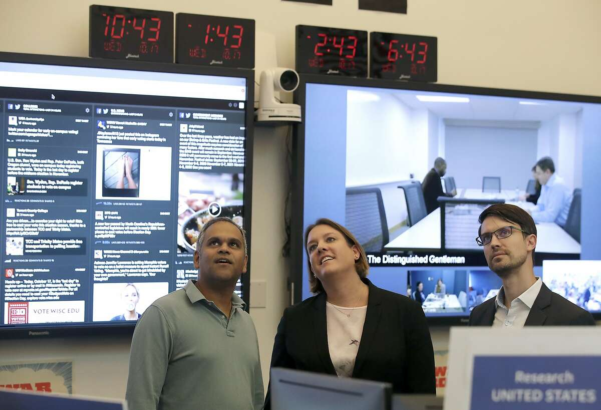 Samidh Chakrabarti, Director of Elections and Civic Engagement, from left, stands with Katie Harbath, Global Politics and Government Outreach Director and Nathaniel Gleicher, Head of Cybersecurity Policy, during a demonstration in the war room, where Facebook monitors election related content on the platform, in Menlo Park, Calif., Wednesday, Oct. 17, 2018. (AP Photo/Jeff Chiu)