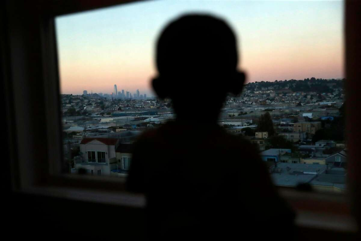3-year-old Z'Allah Evans looks at the San Francisco skyline from the kitchen window of the apartment his family moved into last Monday in San Francisco, Calif..