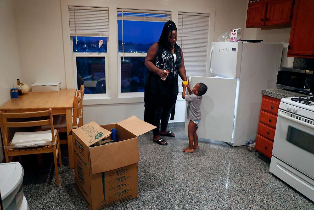 Jacquiline Evans gives her 3-year-old son, Z'Allah Evans, a drink in the kitchen of the apartment they moved into last Monday in San Francisco, Calif..