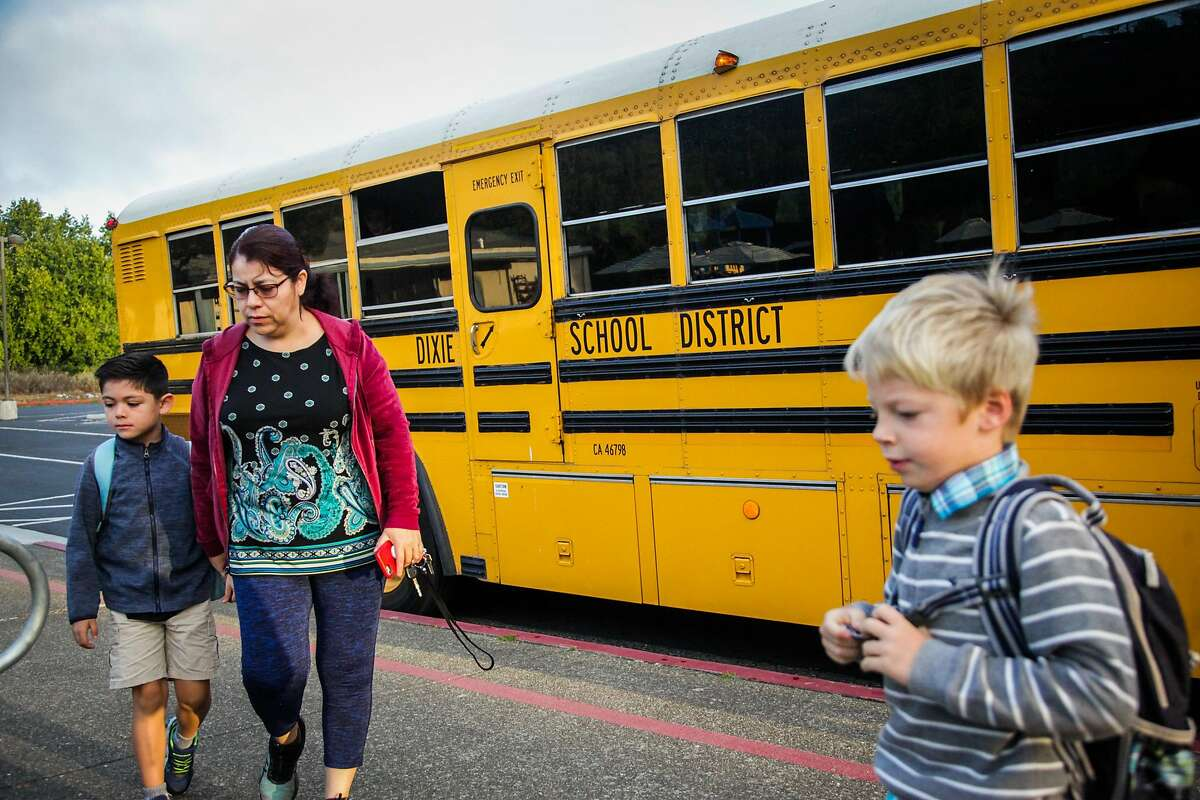 Students make their way into school after getting off the school bus at Dixie Elementary School in San Rafael, California, on Thursday, Oct. 18, 2018.