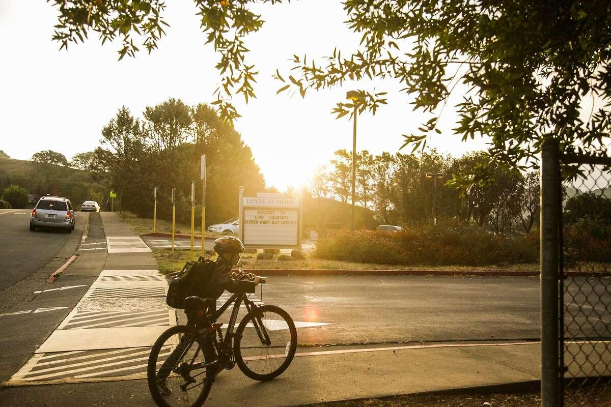 A student walks his bike into Dixie Elementary School in San Rafael, California, on Thursday, Oct. 18, 2018.