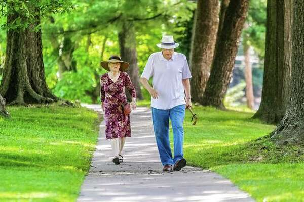 Sen. William R. Haine (D-Alton) takes a quiet stroll in his Middletown neighborhood's Haskell Park with wife Anna this summer. He's now in remission after a battle with cancer, and plans to retire at the end of this term in January.