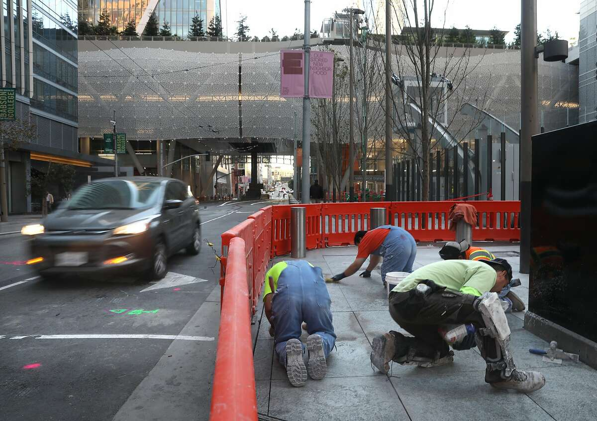 Construction workers pave sidewalks on Fremont at Mission streets at Transbay Transit Center as traffic opens to traffic on Fremont St. on Monday, Oct. 15, 2018 in San Francisco, Calif. The opening of Fremont, between Howard and Mission streets, comes nearly three weeks after cracks were found in steel beams above the motorway.