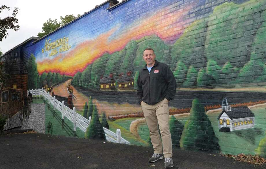 Jason Milligan, owner of Milligan Realty, stands on Friday next to the mural he had painted on his building at 97 Wall St. Photo: Erik Trautmann / Hearst Connecticut Media / Norwalk Hour