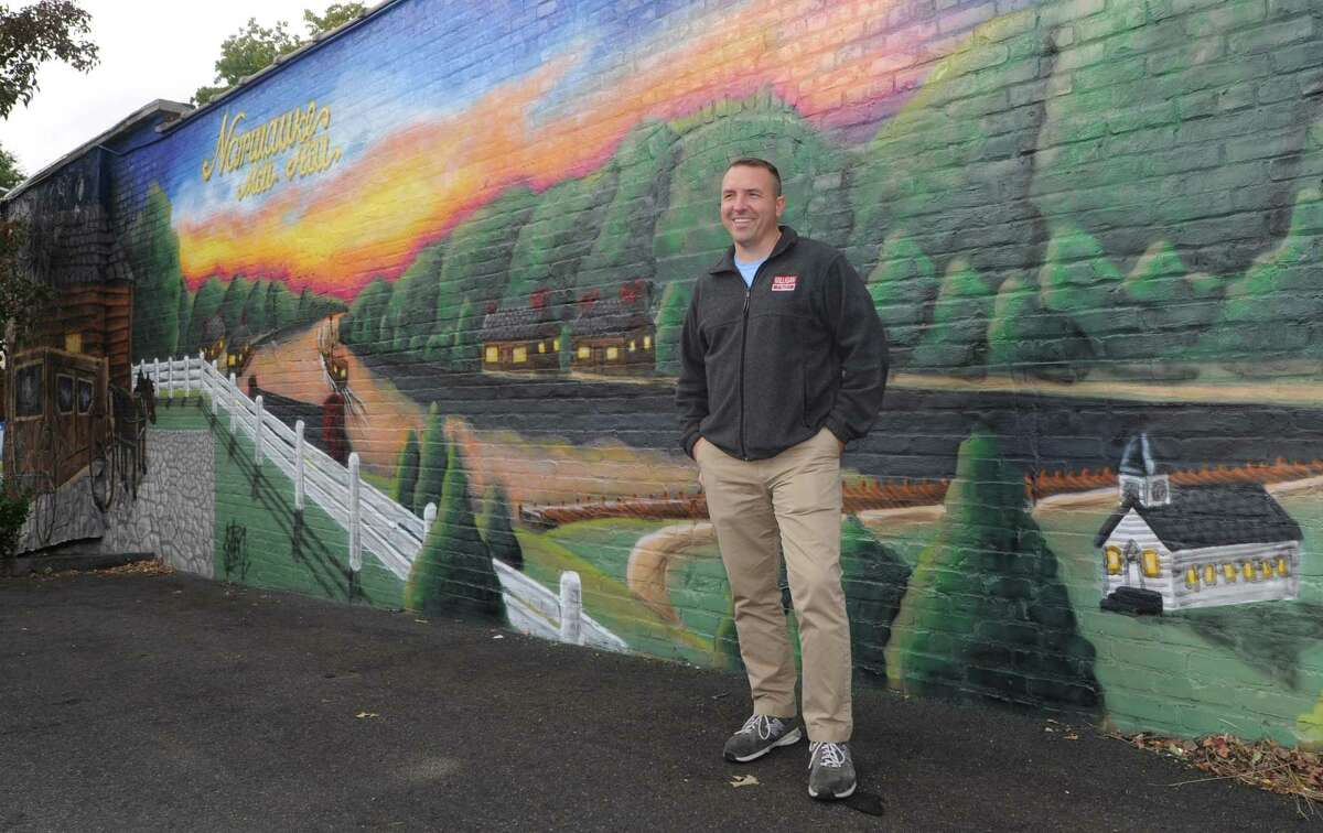 Jason Milligan, owner of Milligan Realty, stands next to the mural he had painted on his building at 97 Wall Street Friday, October 19, 2018, in Norwalk, Conn. The Wall Street Neighborhood Association, to which commercial real-estate developer Jason Milligan belongs, has launched an online petition titled ?'Save the Wall Art on Wall Street?' at change.org. The launch comes after Milligan recently had a mural painted on his property at 97 Wall St. and remains under a zoning violation for the mural he had painted on his building at 21 Isaacs St. Milligan, who remains the subject of a lawsuit after purchasing those and other properties within the stalled Wall Street Place development area,