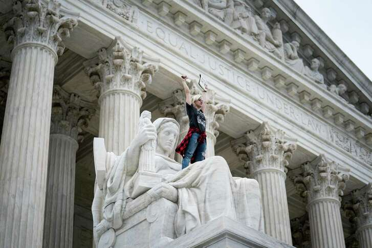 """Demonstrator Jessica Campbell-Swanson of Denver stands on the lap of the """"Contemplation of Justice"""" statue during a protest outside the Supreme Court building, in Washington, Oct. 6, 2018."""
