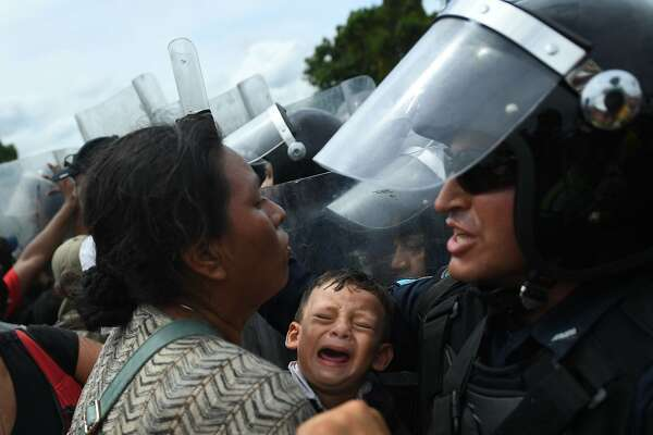 Honduran migrants heading in a caravan to the US, hold up a crying baby while they struggle to cross one of the gates of the Guatemala-Mexico international border bridge in Ciudad Hidalgo, Chiapas state, Mexico, on October 19, 2018. - Honduran migrants who have made their way through Central America were gathering at Guatemala's northern border with Mexico on Friday, despite President Donald Trump's threat to deploy the military to stop them entering the United States. (Photo by Pedro Pardo / AFP)PEDRO PARDO/AFP/Getty Images
