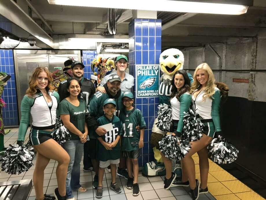 In this October 2018 photo provided by Matt Liston, Philadelphia Eagles fan Jigar Desai poses with his family, friends and members of the Philadelphia Eagles Cheerleaders in front of the subway pillar he ran into earlier this year at Ellsworth Station on the Broad Street subway line in Philadelphia. The moment in the spotlight isn't over yet for Desai who stumbled into fame as a viral video star after running into the subway pillar. Desai is now the subject of an NFL digital short feature, shot ahead of the Oct. 28 Eagles game against the Jacksonville Jaguars in London. (Matt Liston via AP) Photo: Matt Liston / Associated Press / Matt Liston