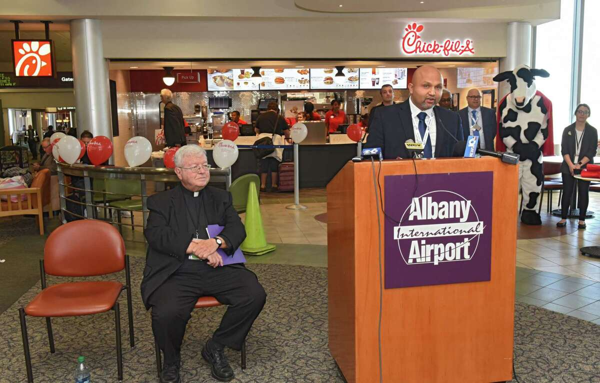 Milan Patel, CEO and president of OHM Concessions Group, speaks as Albany International Airport hosts a Grand Opening Celebration for the area's first Chick-fil-A on Friday, Oct. 19, 2018 in Colonie, N.Y. Rev. Kenneth Doyle, chairman of the Albany County Airport Authority is seen at left. (Lori Van Buren/Times Union)