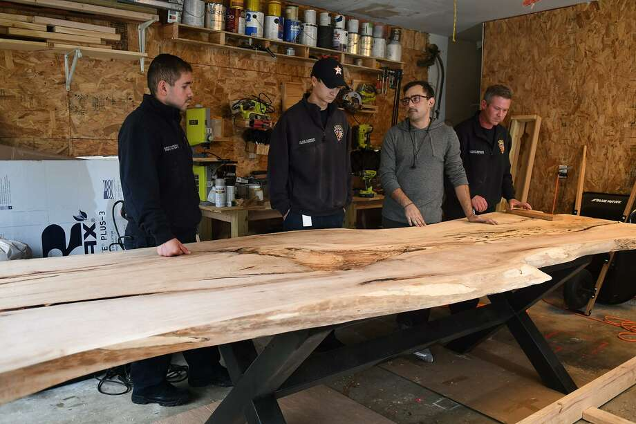 Spring Fire Dept. firefighters Christopher Pedroza, from left, Blake Thompson, Santiago Eckardt, and Mchael Mimshack talk about the live edge elm table that Eckardt is working on his garage for Station 75 on Oct. 17, 2018. Photo: Jerry Baker, Houston Chronicle / Contributor / Houston Chronicle