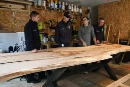Spring Fire Dept. firefighters Christopher Pedroza, from left, Blake Thompson, Santiago Eckardt, and Mchael Mimshack talk about the live edge elm table that Eckardt is working on his garage for Station 75 on Oct. 17, 2018.