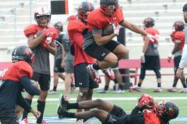 Lamar's Zae Giles (on ground at right) and teammates run drills as they prepare for Saturday's home game against Sam Houston State. Tuesday, October 16, 2018 Kim Brent/The Enterprise