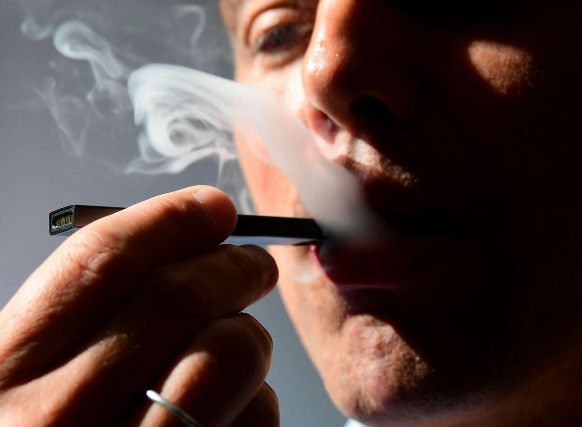 An illustration shows a man exhaling smoke from an electronic cigarette in Washington, DC on October 2, 2018. - In just three years, the electronic cigarette manufacturer Juul has swallowed the American market with its vaporettes in the shape of a USB key. Its success represents a public health dilemma for health authorities in the United States and elsewhere. (Photo by EVA HAMBACH / AFP)EVA HAMBACH/AFP/Getty Images