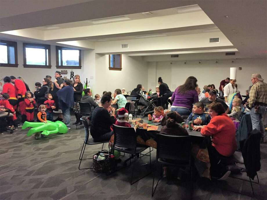 The Torrington Library held a very well-attended Halloween Bash earlier in October. Above, guests enjoy a hot dog and baked goods during the party. Photo: Contributed Photo /