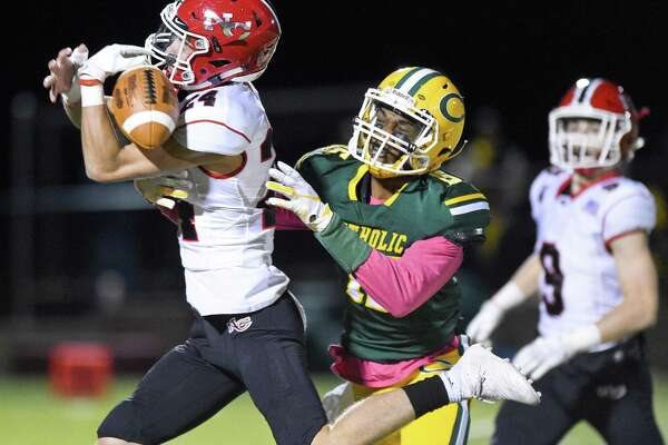 New Canaan defender Charlie Cunney (24) drops a pass intended for Trinity Catholic's Anthony Anderson during the first half in Stamford on Friday. New Canaan won 49-7.