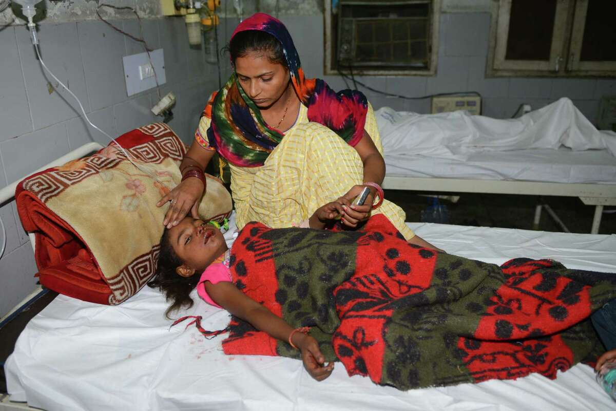 Khushi, an injured Indian patient, is comforted by her mother Parmjit, as she recovers after a train accident at the Guru Nanak Dev Hospital in Amritsar on October 19, 2018. - A speeding train ran over revellers watching fireworks during a Hindu festival in northern India on October 19, 2018, killing more than 50 people, with eyewitnesses saying they were given no warning before disaster struck. (Photo by NARINDER NANU / AFP)NARINDER NANU/AFP/Getty Images