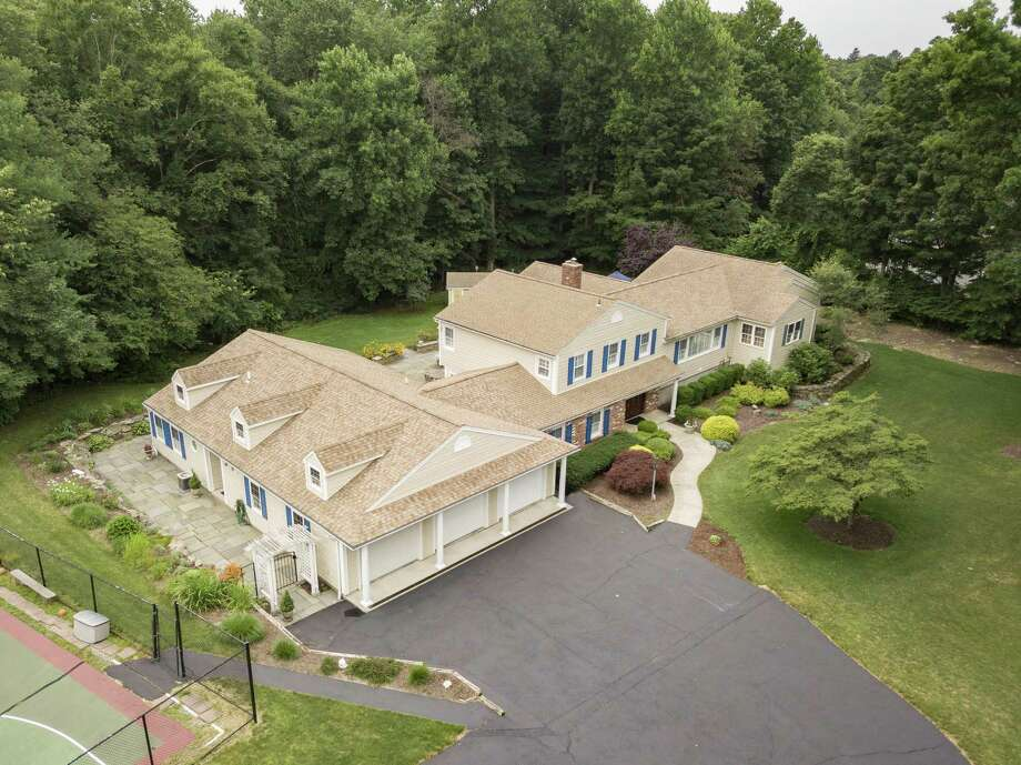 The split-level home at 455 Stonehouse Road in Trumbull is set on a 1.15-acre lot surrounded by stone walls, extensive plantings and mature trees for an abundance of privacy. The lush, level lawn offers plenty of room for recreation. Photo: Real Estate Two / ONLINE_CHECK