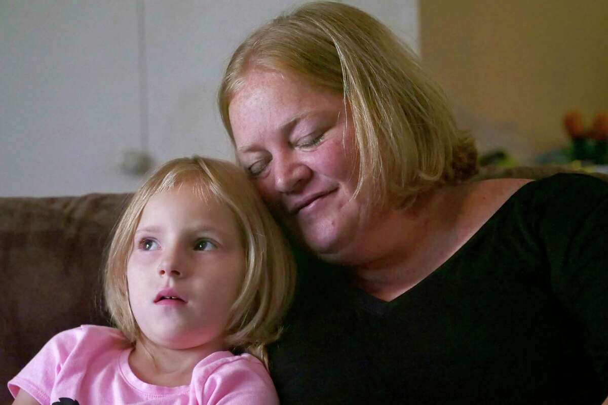 In this July 11, 2018, photo, Bridgett Snelten sits with her daughter Bella at their home in Sandy, Utah. Snelten has diabetes and has had to change health insurance plans three years in a row. Twice, new insurers wouldn?'t cover Trulicity, a once-a-week injected diabetes medicine she?'d been taking that helped control her blood sugar tightly. Instead, they made her return to an inexpensive, twice-a-day injected diabetes drug she and her doctor knew didn?'t work for her. (AP Photo/Rick Bowmer)