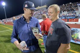 Major League Baseball pitcher and Lumberton grad Clay Buchholtz shares a cell phone moment with his father after participating in the pregame coin toss at the Raiders homecoming game on Friday night against Livingston. Photo taken Friday, October 19, 2018 Drew Loker/Speical to The Enterprise
