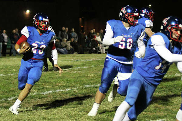 Carlinville running back Ethan Wallace (left) finds running room behind blockers Nick Walton (right) and Blaze Ballowe in the first half of the Cavs' 66-0 victory over Greenville on Friday night in Carlinville.