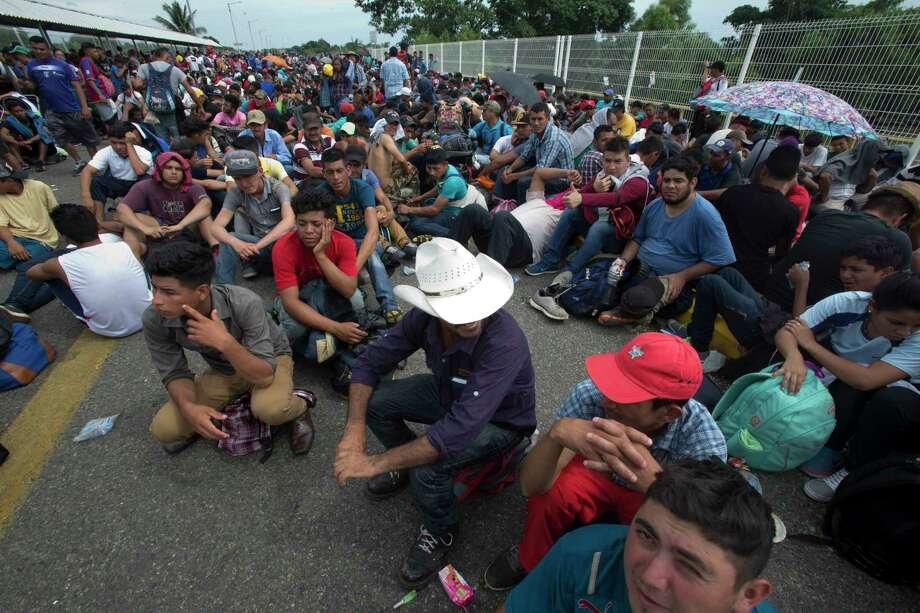 Central American migrants sit on the bridge over the Suchiate River that separates Guatemala and Mexico, in Tecun Uman, Guatemala, Friday, Oct. 19, 2018. Central Americans traveling in a mass caravan broke through a Guatemalan border fence and streamed by the thousands toward Mexican territory, defying Mexican authorities' entreaties for an orderly migration and U.S. President Donald Trump's threats of retaliation. Photo: Moises Castillo, AP / Copyright 2018 The Associated Press. All rights reserved