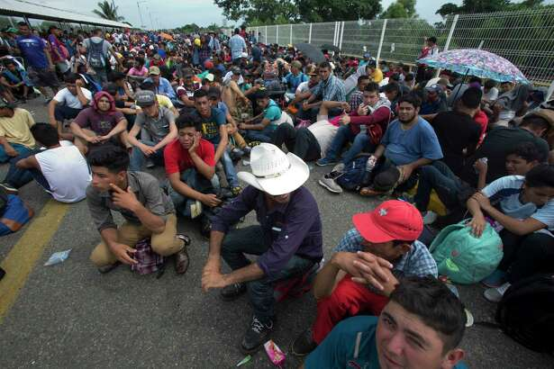 Central American migrants sit on the bridge over the Suchiate River that separates Guatemala and Mexico, in Tecun Uman, Guatemala, Friday, Oct. 19, 2018. Central Americans traveling in a mass caravan broke through a Guatemalan border fence and streamed by the thousands toward Mexican territory, defying Mexican authorities' entreaties for an orderly migration and U.S. President Donald Trump's threats of retaliation.