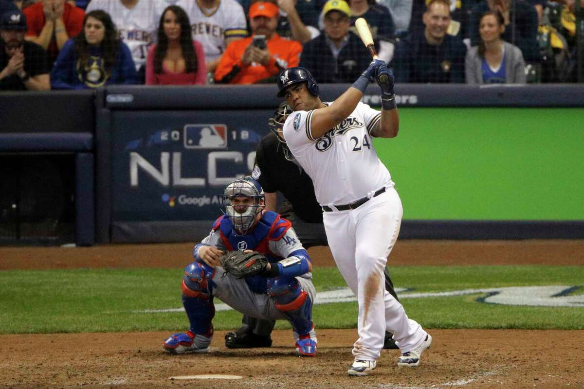 Milwaukee Brewers' Jesus Aguilar (24) hits an RBI single during the eighth inning of Game 6 of the National League Championship Series baseball game against the Los Angeles Dodgers Friday, Oct. 19, 2018, in Milwaukee. (AP Photo/Charlie Riedel)