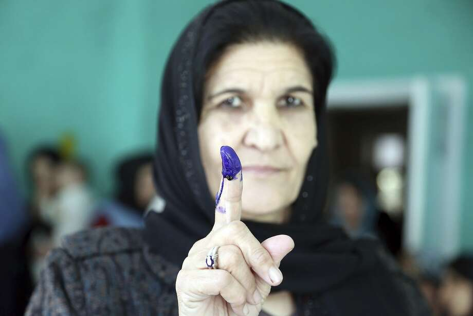 An Afghan woman shows her inked finger after casting her vote at a polling station during the Parliamentary elections in Kabul, Afghanistan, Saturday, Oct. 20, 2018. Tens of thousands of Afghan forces fanned out across the country as voting began Saturday in the elections that followed a campaign marred by relentless violence. (AP Photo/Rahmat Gul) Photo: Rahmat Gul / Associated Press