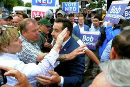 Lori Pelletier, president of the Connecticut AFL-CIO, left, and JR Romano, Republican Party Chairman, center, confront each other amid a rowdy crowd of Ned Lamont and Bob Stefanowski supporters during a rally organized by area unions prior to a gubernatorial debate in in New London in September.