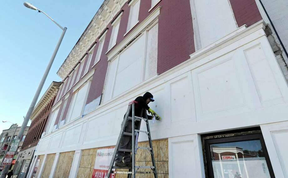 A painter calks the exterior of Ganga Duleep's building at 45 Wall St. Thursday, October 18, 2018, in Norwalk, Conn. Scaffolding was removed Oct. 16 from the exterior of the building a which was gutted by a fire in August 2010. While restoration work continues inside, the removal of the scaffolding, painting of the exterior of the building and posting of a leasing sign outside are welcome signs for neighbors who had long considered the fire-damaged building an example of neighborhood blight. Photo: Erik Trautmann / Hearst Connecticut Media / Norwalk Hour