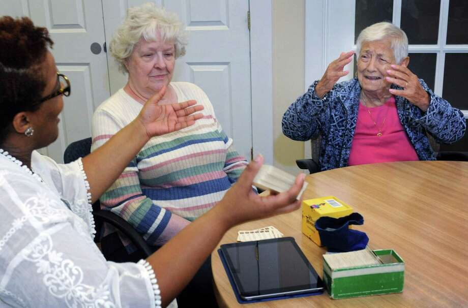 Elderhouse employee April Mattison reads trivia questions to clients including a Johnson and Viola Fretina as they participate in activity time Thursday, September 20, 2018, at the facility in Norwalk, Conn. ElderHouse is a nonprofit day care center that offers medical and social services during the day. The organization provides a safe environment to elders and gives caregivers a break during the day Photo: Erik Trautmann / Hearst Connecticut Media / Norwalk Hour