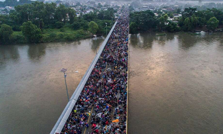 TOPSHOT - Aerial view of a Honduran migrant caravan heading to the US, on the Guatemala-Mexico international border bridge in Ciudad Hidalgo, Chiapas state, Mexico, on October 20, 2018. - Thousands of migrants who forced their way through Guatemala's northwestern border and flooded onto a bridge leading to Mexico, where riot police battled them back, on Saturday waited at the border in the hope of continuing their journey to the United States. (Photo by PEDRO PARDO / AFP)PEDRO PARDO/AFP/Getty Images Photo: PEDRO PARDO;Pedro Pardo / AFP / Getty Images