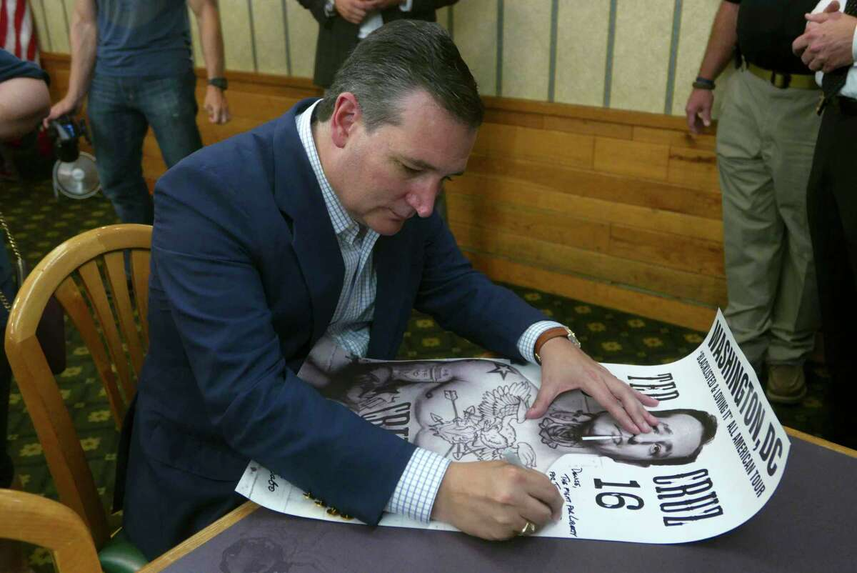 U.S. Senator Ted Cruz, R-Texas, autographs a poster designed by conservative artist Sabo after speaking at Underwood's BBQ in Brownwood, Texas, on Thursday, Aug. 9, 2018.