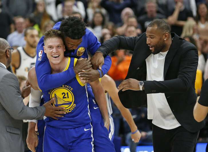 Golden State Warriors' Jonas Jerebko (21) celebrates after scoring the winning shot against the Utah Jazz, with teammates Jordan Bell, rear, and DeMarcus Cousins, right, in the second half during an NBA basketball game Friday, Oct. 19, 2018, in Salt Lake City. (AP Photo/Rick Bowmer)
