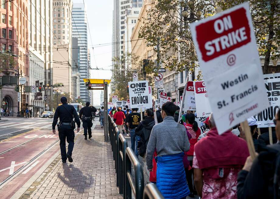 San Francisco police officers escort a march by Unite Here union members who are on strike at seven San Francisco hotels. Photo: Jessica Christian / The Chronicle