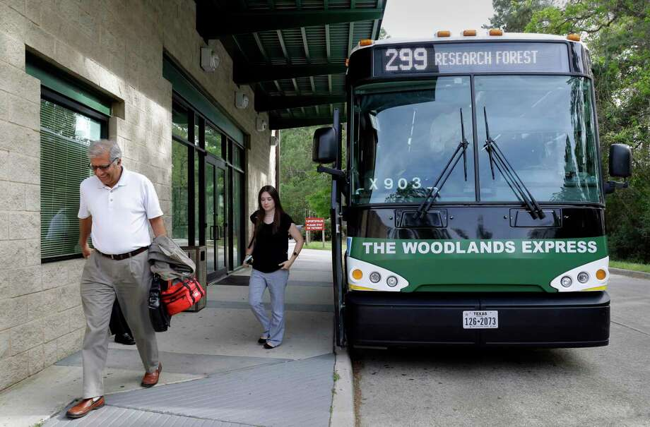 """Communters exit one of the buses of The Woodlands Express, a commuter bus service to Houston, at the Marisco Place """"Park and Ride"""" location in The Woodlands, in March 2018. Officials with the township's Transit Program unveiled a new bus tracking app this week called """"Next Bus."""" Photo: Michael Wyke, Freelance / For The Chronicle / © 2018 Houston Chronicle"""