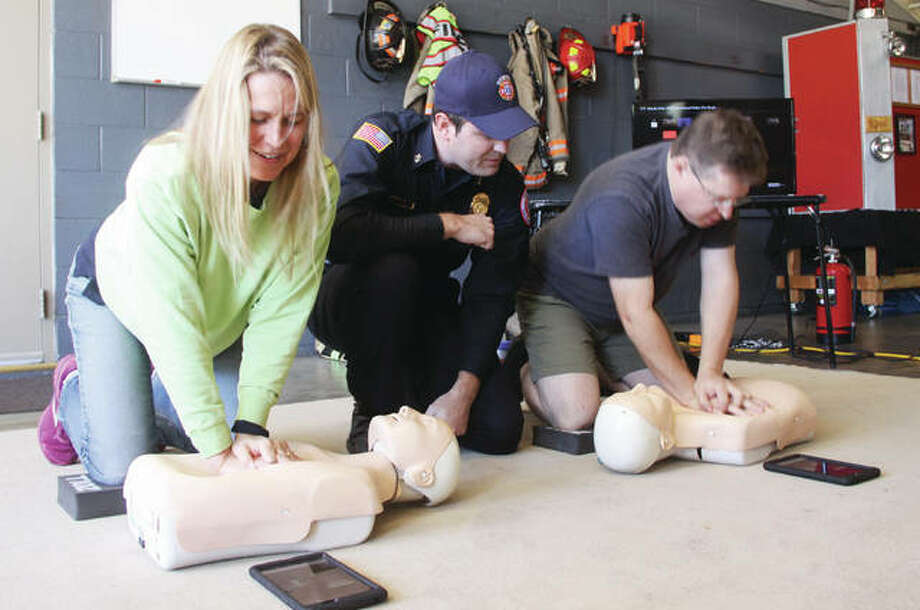 Stephanie Church Hein and Austin Hein practice compressions on CPR dummies with the help of Godfrey Fire Chief Erik Kambarian during the departments open house Saturday. The event was held at Station 2 and featured a number of exhibits. A major emphasis was on CPR, in part because of Sudden Cardiac Arrest Awareness Month. Photo: Scott Cousins | The Telegraph